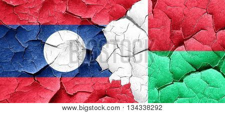 Laos flag with Madagascar flag on a grunge cracked wall