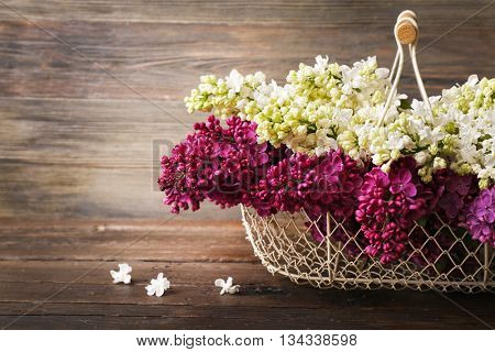 Basket with fresh lilac on wooden background