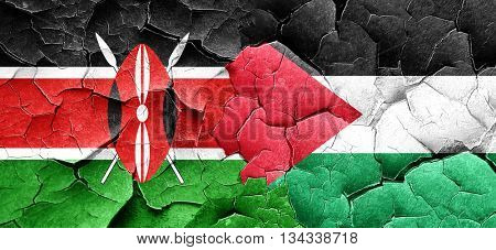 Kenya flag with Palestine flag on a grunge cracked wall