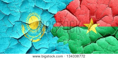 Kazakhstan flag with Burkina Faso flag on a grunge cracked wall