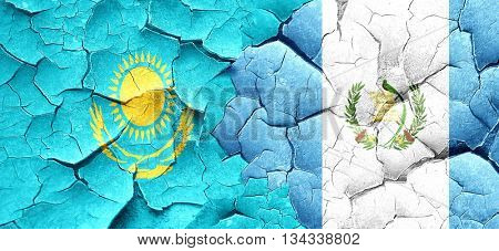 Kazakhstan flag with Guatemala flag on a grunge cracked wall