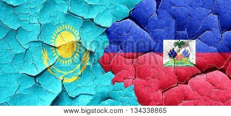 Kazakhstan flag with Haiti flag on a grunge cracked wall
