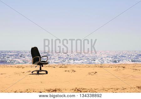 An office chair on the beach