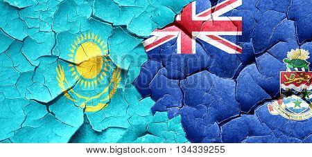 Kazakhstan flag with Cayman islands flag on a grunge cracked wal