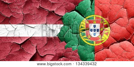 Latvia flag with Portugal flag on a grunge cracked wall