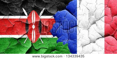 Kenya flag with France flag on a grunge cracked wall