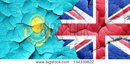 Kazakhstan flag with Great Britain flag on a grunge cracked wall