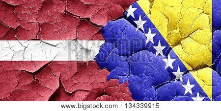 Latvia flag with Bosnia and Herzegovina flag on a grunge cracked
