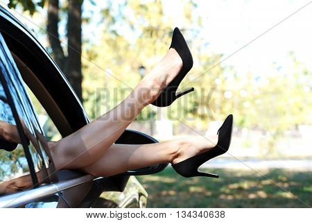 Woman's legs out of the car window.