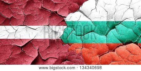 Latvia flag with Bulgaria flag on a grunge cracked wall
