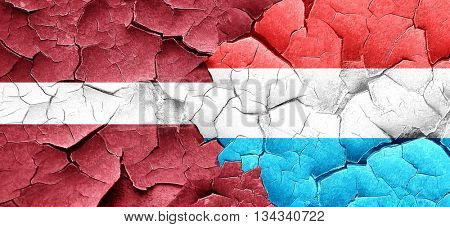 Latvia flag with Luxembourg flag on a grunge cracked wall