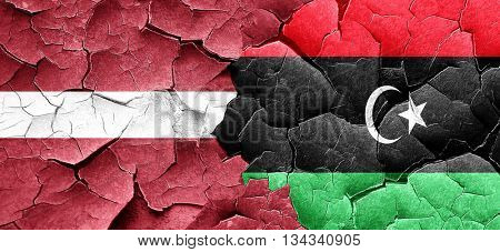 Latvia flag with Libya flag on a grunge cracked wall