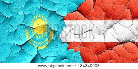 Kazakhstan flag with Austria flag on a grunge cracked wall