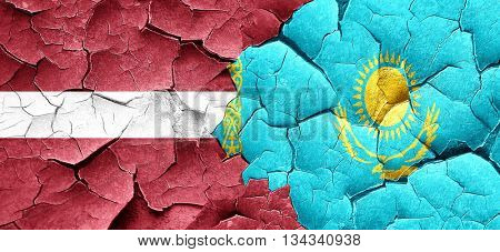 Latvia flag with Kazakhstan flag on a grunge cracked wall