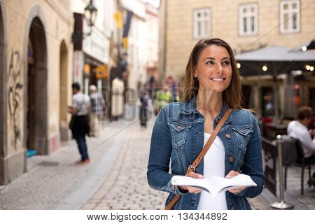 young traveller sightseeing holding a guide book