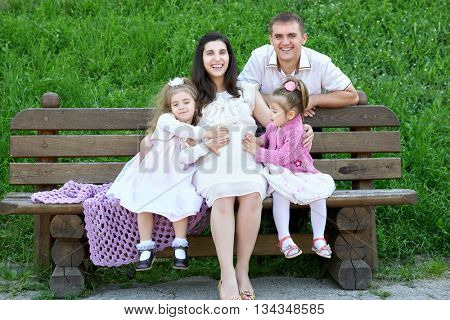 family on outdoor, pregnant woman with child and husband, city park, summer season, green grass and trees