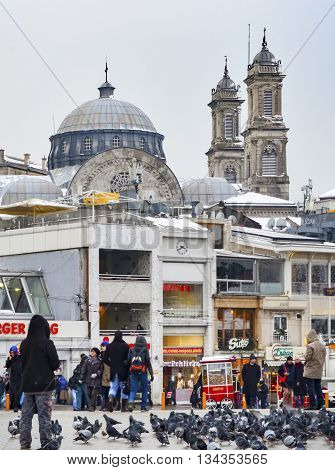 Istanbul Turkey - December 21 2012: Taksim Square cold and snowy winter day. Hagia Triada Greek Orthodox Church in the background. The Hagia Triada Greek Orthodox church in Istanbul Turkey. The building was erected in 1880 and is considered the largest Gr