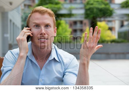 Closeup portrait young man annoyed frustrated pissed off by someone talking on his mobile phone bad news isolated outdoors outside background. Long wait times horrible conversations concept
