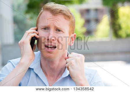 Closeup portrait worried young man in blue shirt talking on phone to someone looking gloomy isolated outdoors outside background