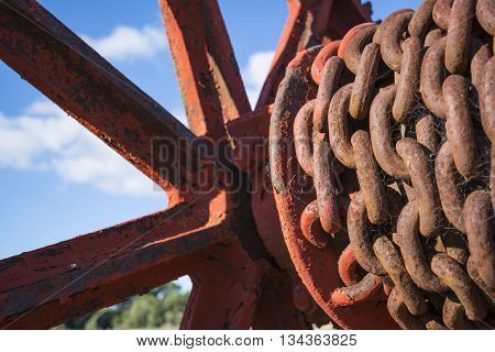 Rusting chains complete with spider webs and cracking peeling paint on an old metal hoist that was found at the Old Burra Railway Station South Australia. Very shallow focus on just the closest chains.