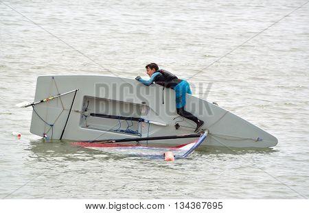 Felixstowe, Suffolk, England - June 11, 2016: Capsized Sailing Dinghy with young man try to right it, in the sea at Felixstowe Suffolk England.