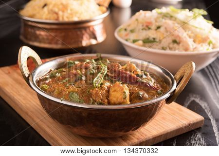 Paneer Butter Masala in a brass bowl on a wooden panel