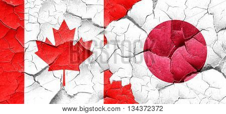 Canada flag with Japan flag on a grunge cracked wall