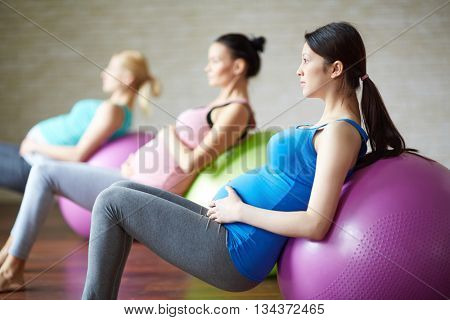 Three pregnant women with exercise balls in gym