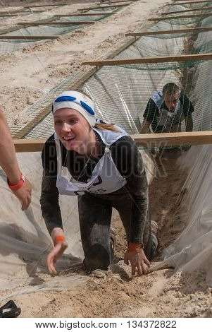 Tyumen Russia - June 11 2016: Race of Heroes project on the ground of the highest military and engineering school. Guardroom stage. Girl leaves entrenchment with sand and water under net