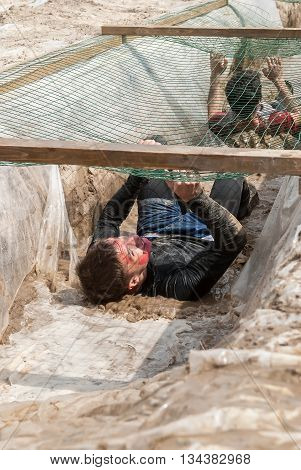 Tyumen Russia - June 11 2016: Race of Heroes project on the ground of the highest military and engineering school. Guardroom stage. Men creep on an entrenchment with sand and water under net
