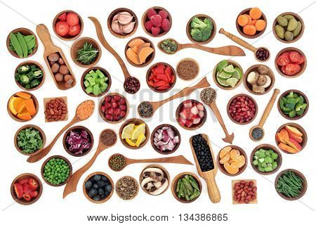 Health and super food of fruit, nuts, seeds and vegetables in wooden bowls and spoons over white background, high in vitamins, antioxidants, anthocyanins and minerals.
