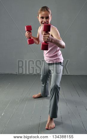Teenage sportive girl is doing exercises with dumbbells to develop with dumbbells muscles on grey background. Sport healthy lifestyle concept. Sporty childhood. Full length portrait of teenager child exercising with weights.