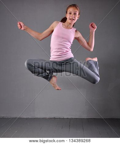 Healthy young muscular teenage girl dancer skipping jumping and dancing in grey studio. Child exercising. Sport healthy lifestyle concept. Sporty childhood.