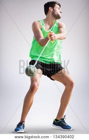 Sportsman throwing a hammer against grey background