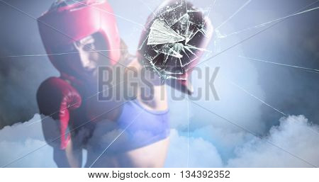 Female boxer with gloves and headgear punching against cloudy sky