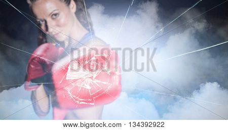 Portrait of athlete with fighting stance against cloudy sky