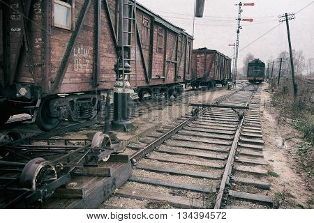 Stylized picture vintage train station with wagons on the rails and telegraph poles on a cloudy day