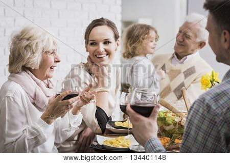 Happy multi-generational family gathering during holidays at the table poster