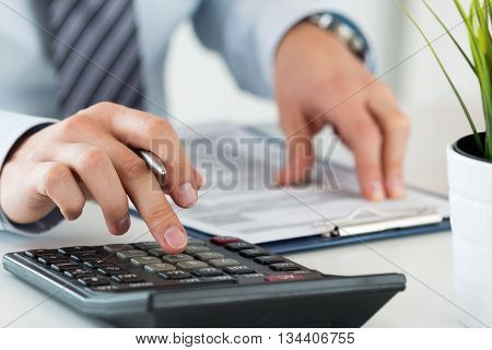 Close up of male accountant or banker calculating or checking balance. Bookkeeper or financial inspector making financial report. Home finances investment economy saving money or insurance concept