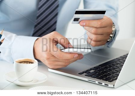 Close up view of businessman hands holding credit card and making online purchase using mobile phone. Shopping consumerism delivery financial security anti-fraud or internet banking concept.