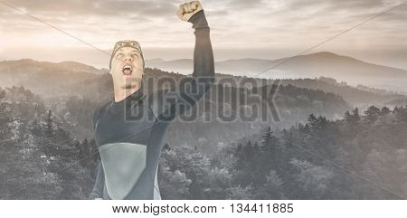 Swimmer posing after victory against trees and mountain range against cloudy sky