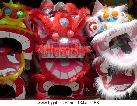 Close up of three colourful Vietnamese festival masks with typical wide eyes and excited expressions