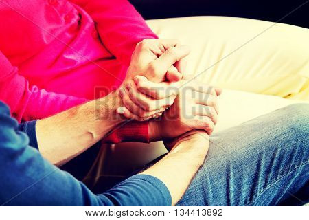 Mother and son sitting on couch and holding hands