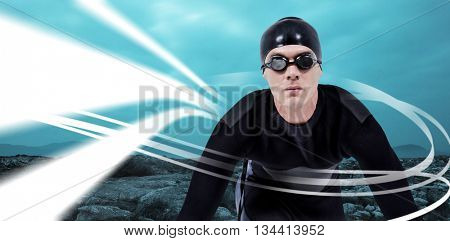 Confident swimmer in wetsuit against majestic shot of trees and mountain range against cloudscape