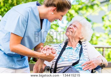 Nurse holding hand of senior woman in pension home poster