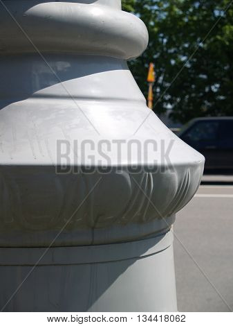Closeup of marble column base against city street abd trees
