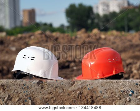 Orange helmet builder and a white helmet engineer. Helmets lie on a concrete block on the background of the wasteland. In the distance the city houses. Future construction planning.