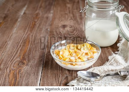 Breakfast with corn flakes and milk in rural style. Glass bowl with corn flakes and glass with milk on wooden brown background in rustic style. horizontal, colorfull