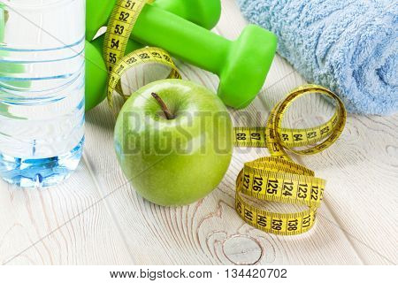 Healthy food and fitness. Apple, dumbells, water bottle and tape measure