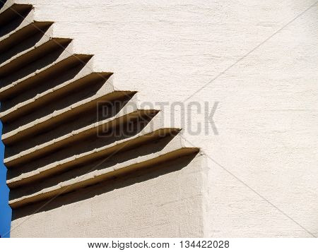 Beautiful textured plastered surface of a brick facade with architectural decor on a corner. Abstract geometric composition formed by the deep shadows and bright light contrast